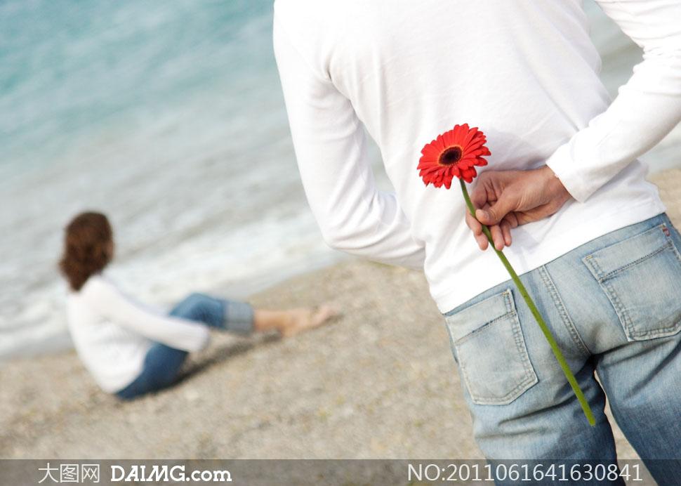 手拿红色雏菊的男人背影高清摄影图片